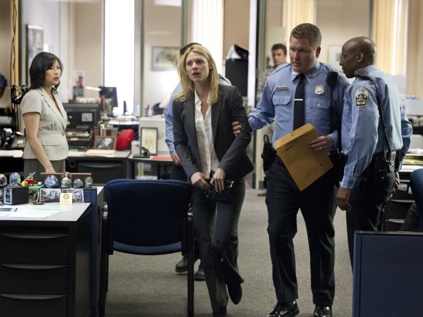 """Police officers detain CIA case officer Carrie Mathison (Claire Danes) when she tries to reveal classified information to a newspaper reporter on """"Homeland."""""""