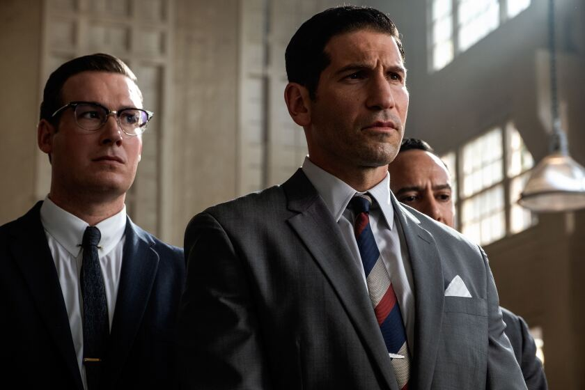 "Jon Bernthal as Lee Iacocca in ""Ford v Ferrari,"" with two other men in suits standing behind him."