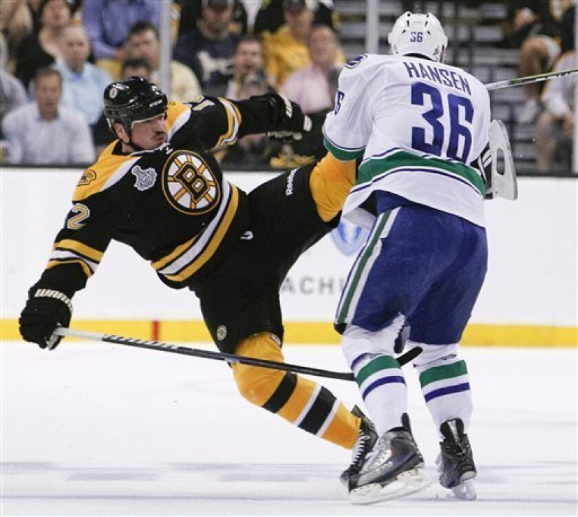 Boston Bruins defenseman Tomas Kaberle (12) collides with Vancouver Canucks right wing Jannik Hansen (36) in the first period during Game 3 of the NHL hockey Stanley Cup Finals, Monday, June 6, 2011, in Boston. (AP Photo/Elise Amendola)