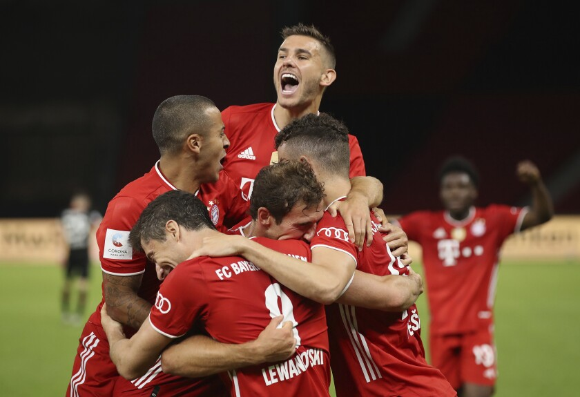 Munich's Robert Lewandowski , center bottom, celebrates with teammates after scoring his team's fourth goal during the DFB Cup final match between Bayer 04 Leverkusen and FC Bayern Muenchen at Olympiastadion in Berlin, Germany, Saturday, July 4, 2020. (Photo by Alexander Hassenstein/Pool via AP)