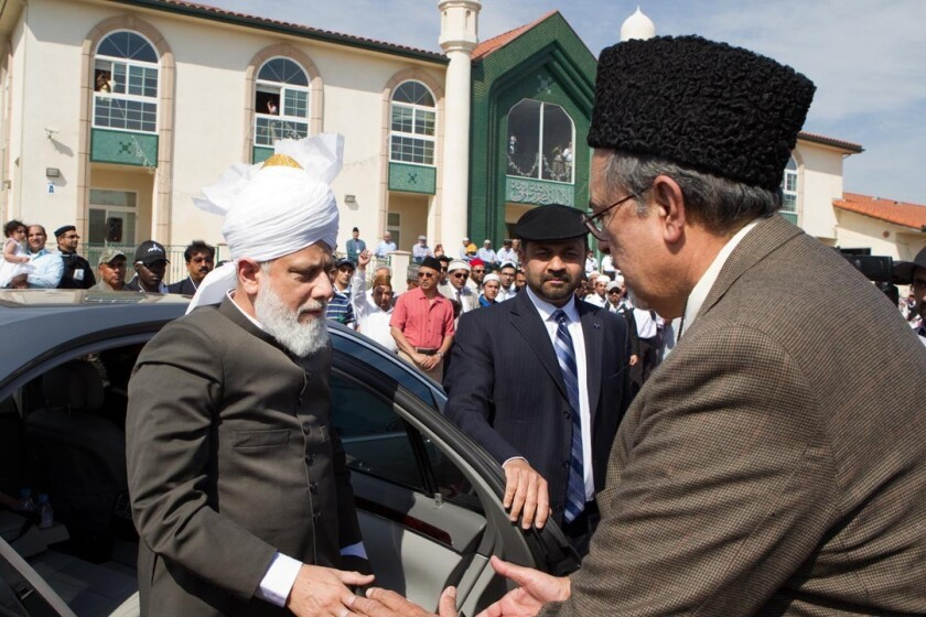 Hadhrat Mirza Masroor Ahmad, the global leader of the 124-year-old Ahmadiyya Muslim Community, is greeted by the religion's U.S. national president, Ahsanullah Zafar, upon arrival at the Baitul Hameed Mosque in Chino.