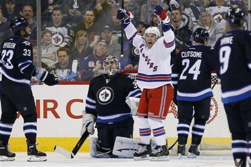 New York Rangers forward Ryan Callahan (24) celebrates his goal against Winnipeg Jets goalie Ondrej Pavelec (31) during the second period of their NHL hockey game, Thursday, March 14, 2013,in Winnipeg, Manitoba. (AP Photo/The Canadian Press, John Woods)