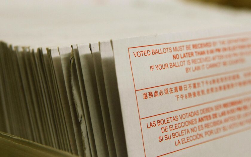 A stack of vote-by-mail ballots sit in a box