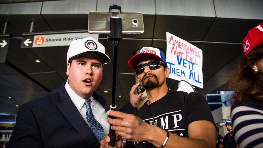 Congressional candidate Omar Navarro, left, and Trump supporter Harim Uziel livestream their counterprotest after thousands showed up at Los Angeles International Airport in February to object to Trump's ban of immigrants from seven majority-Muslim countries.