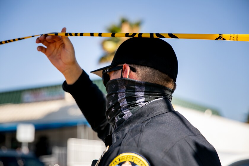 """A San Diego police officer wearing a """"thin blue line"""" mask responds to a shooting by police on Menlo Avenue on July 9."""