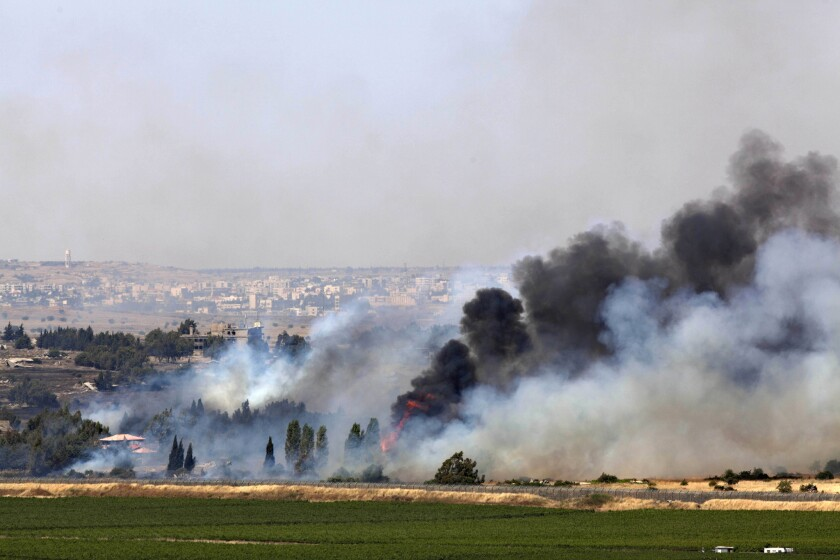 Smoke rises from the Syrian village of Quneitra, near the border with Israel, from fighting between Syrian government troops and rebels Thursday in the U.N.-patrolled Golan Heights.
