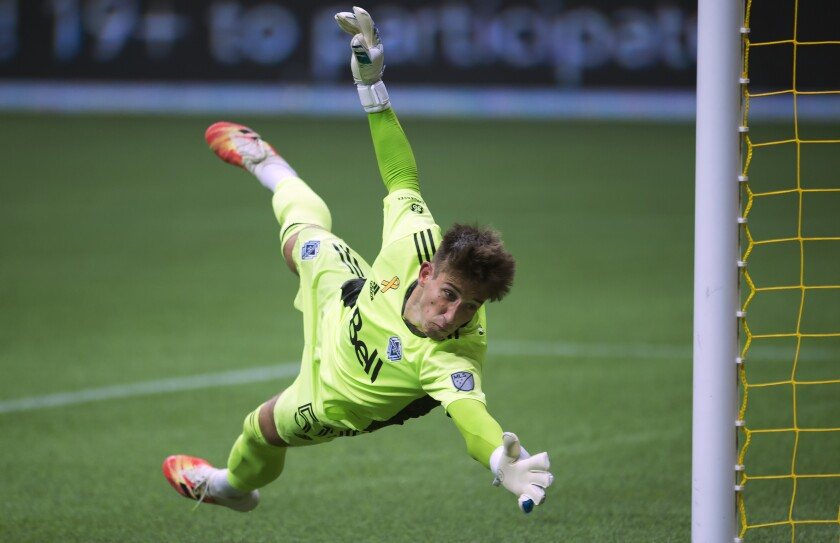 Vancouver Whitecaps goalkeeper Thomas Hasal (51) makes a save against the Montreal Impact during the first half of an MLS soccer game, Sunday, Sept. 13, 2020, in Vancouver, British Columbia. (Jonathan Hayward/The Canadian Press via AP)