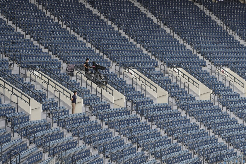 A TV cameraman works in rows of empty seats without fans as a precautionary measure during the KBO league baseball game between KT Wiz and Doosan Bears in Seoul, South Korea, Sunday, Aug. 16, 2020. Fans are banned once again from professional baseball and soccer games, which had just begun to slowly bring back spectators in late July. (AP Photo/Lee Jin-man)