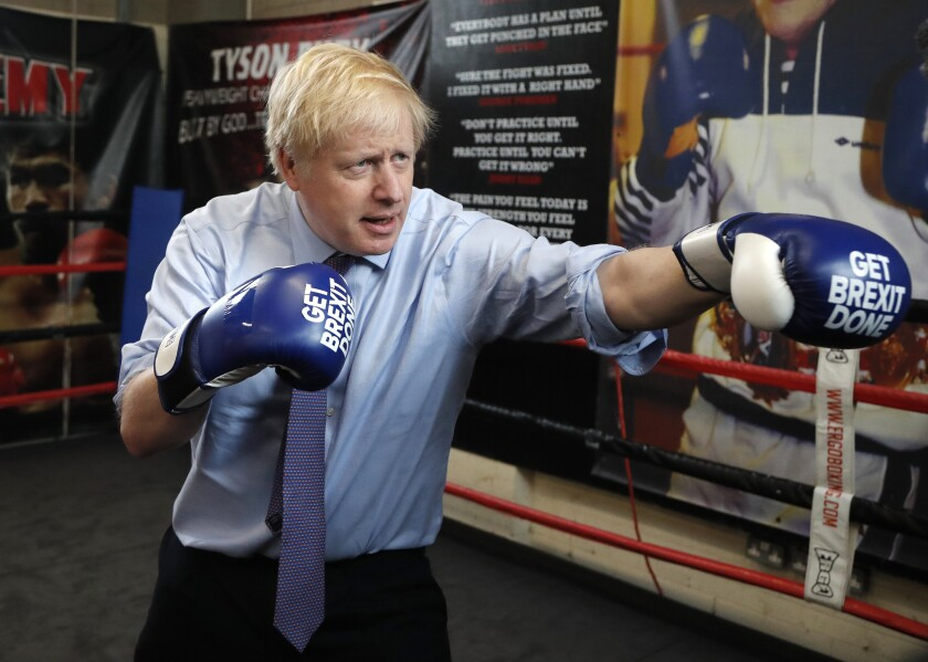 FILE - In this Tuesday, Nov. 19, 2019 file photo Britain's Prime Minister Boris Johnson poses for a photo wearing boxing gloves during a stop in his General Election Campaign trail at Jimmy Egan's Boxing Academy in Manchester, England. (AP Photo/Frank Augstein, File)