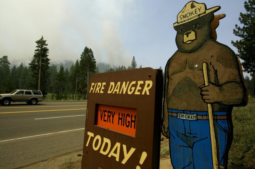 FILE - This June 26, 2007 file photo shows a sign depicting U.S. Forest mascot Smokey Bear on a fire danger sign in South Lake Tahoe, Calif., as smoke from a wildfire rises behind it.  The U.S. Forest Service has abruptly decided not to spend $10 million on a five-year nationwide public relations c