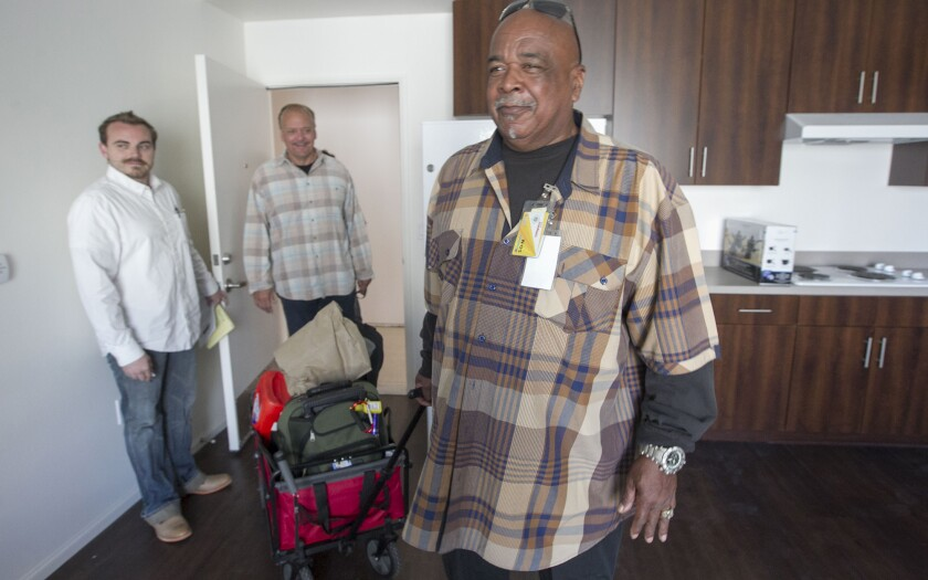 Army veteran Calvin McGary, 66, right, looks around his new one-bedroom unit at the new, not quite trimmed out, Alpha Lofts apartments in the 3800 block of El Cajon Blvd in Normal Heights. The 52-unit complex is for formerly homeless veterans and is run by the Alpha Project. Property manager Frank Tarantino is at far left and Alpha Project CEO Bob McElroy is in the doorway.