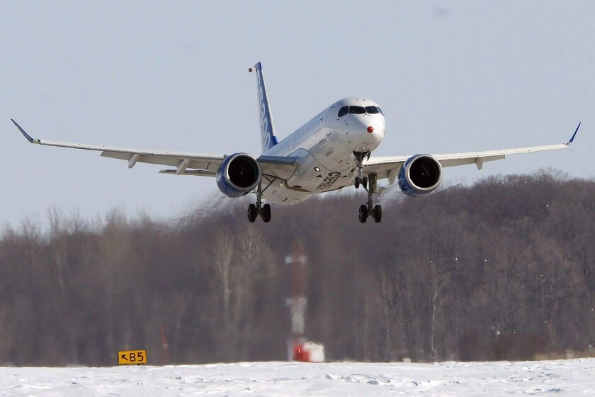 CORRECTS PERCENTAGE OF WORKFORCE TO BE LAID OFF TO ABOUT 10 PERCENT INSTEAD OF 11 PERCENT - In this Feb. 27, 2015 photo, a Bombardier CS300 makes it's maiden test flight in Mirabel, Quebec. Bombardier announced Wednesday, Feb. 17, 2016, it will cut approximately 7,000 jobs, or about 10 percent of i