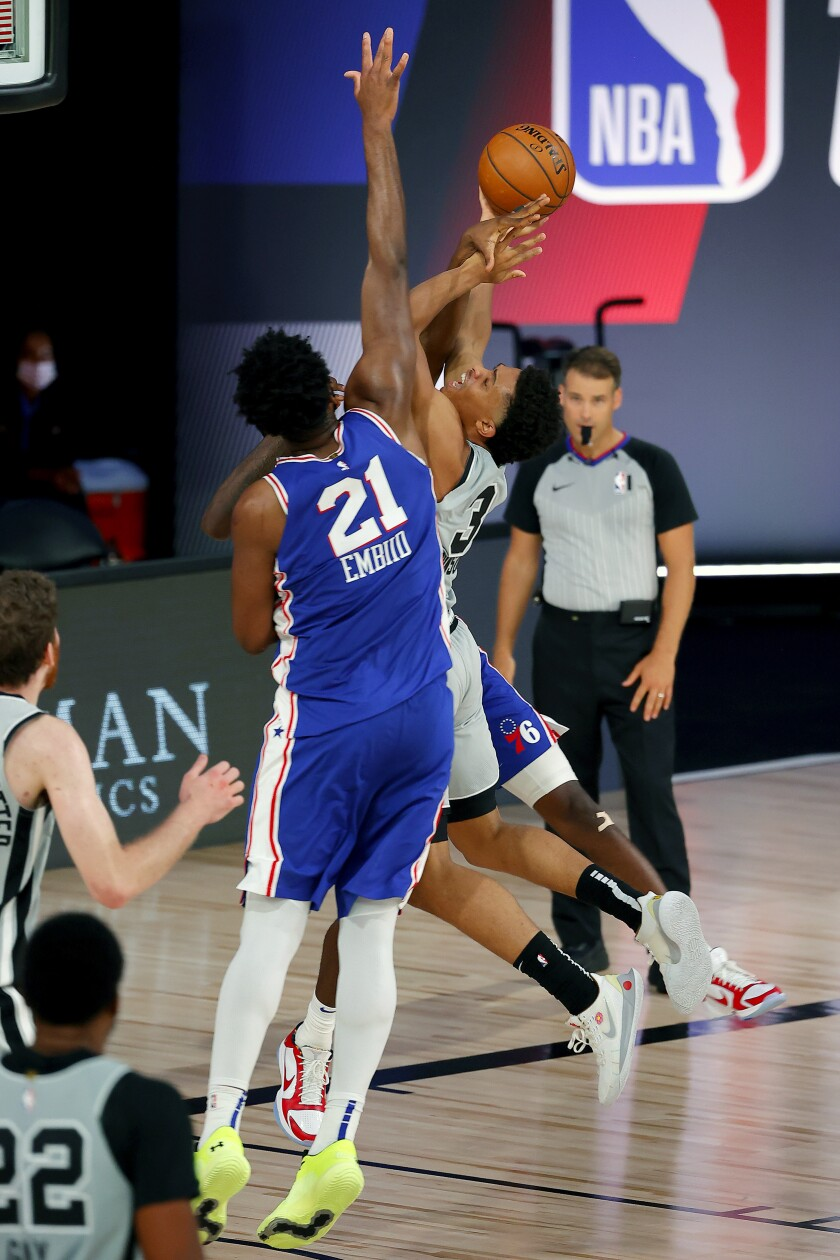 San Antonio Spurs Keldon Johnson (3) attempts a shot against Philadelphia 76ers Joel Embiid (21) during the second half of an NBA basketball game Monday, Aug. 3, 2020, in Lake Buena Vista, Fla. (Mike Ehrmann/Pool Photo via AP)