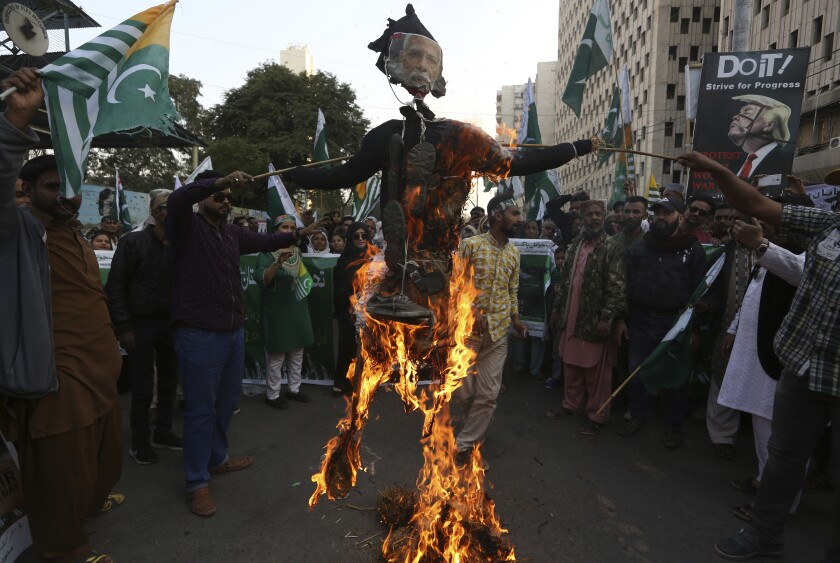 Protesters burn an effigy of Indian prime minister during a rally to express solidarity with Indian Kashmiris struggling for their independence, in Karachi, Pakistan, Wednesday, Feb. 5, 2020. Pakistan's prime minister urged the international community to live up to its obligation and ensure the freedom of the Kashmiri people. (AP Photo/Fareed Khan)