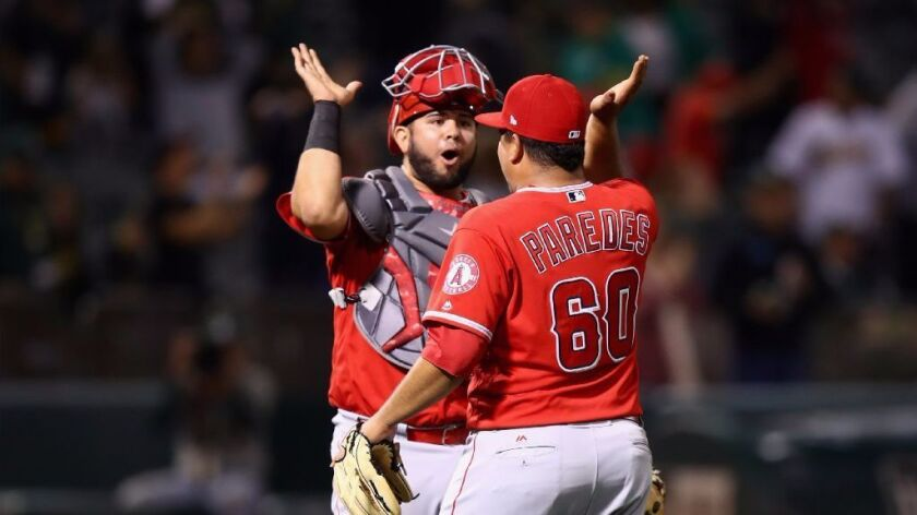 Angels catcher Juan Graterol and reliever Eduardo Paredes celebrate after getting the final out in t