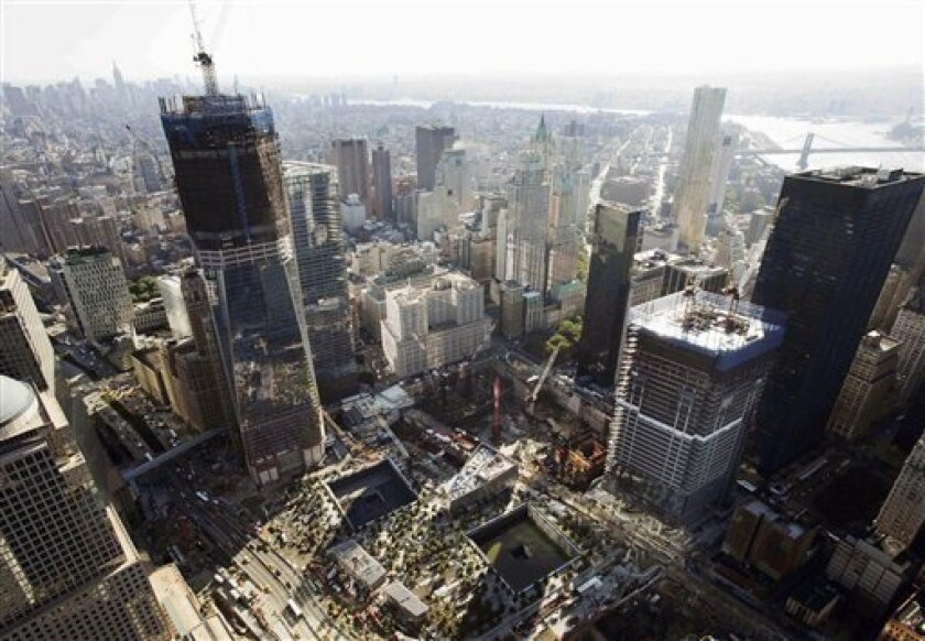 In this July 27, 2011 aerial file photo, construction continues at the World Trade Center in New York. One World Trade Center, left, rises above the lower Manhattan skyline followed by Four World Trade Center, lower right, with the square outlines of the almost-completed September 11 Memorial at lower center. (AP Photo/Mark Lennihan, File)