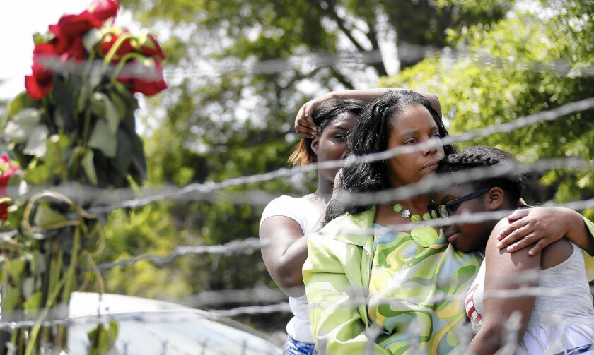 Waynetta Theodore, left, Alberta Harris and Christiena Preston pay their respects on May 10 at a memorial near the site in Hattiesburg, Miss., where two police officers were killed during a traffic stop.