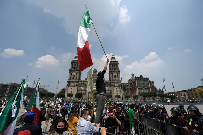 A member of the National Front Anti-AMLO (Frena) holds up a Mexican flag in front of a line of riot police