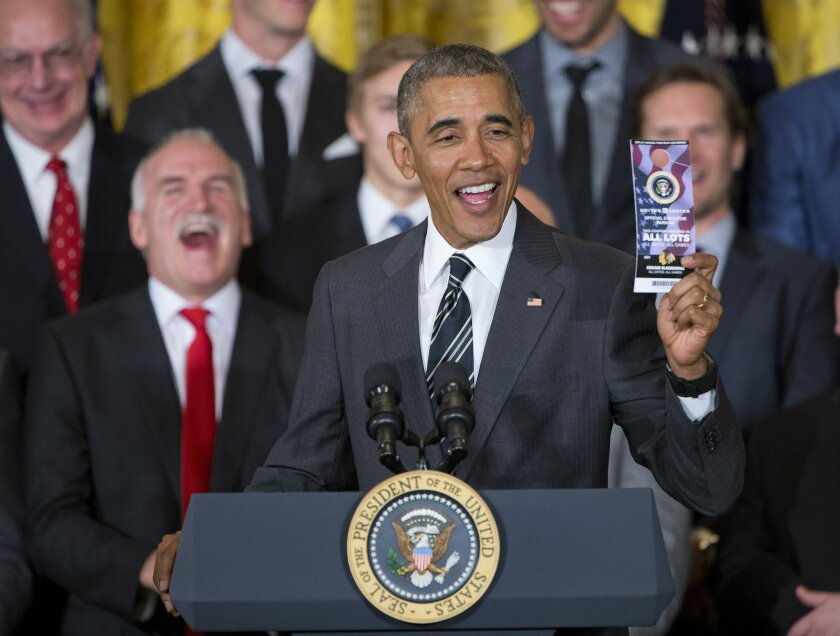 President Barack Obama holds up a parking pass that was presented to him during a ceremony to honor the 2015 NHL Stanley Cup Champion Chicago Blackhawks in the East Room of the White House in Washington, Thursday, Feb. 18, 2016. The parking pass is good for all games and all dates at the United Cen