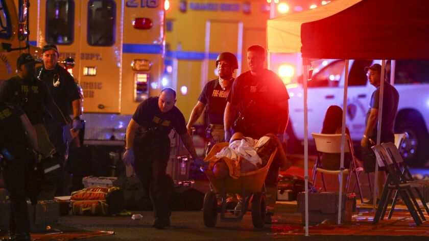 A wounded person is walked in on a wheelbarrow as Las Vegas police respond during an active shooter