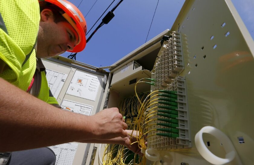 Frontier Communications technician Airik Morales checks a utility box that serves as a hub for the company's network in Long Beach.