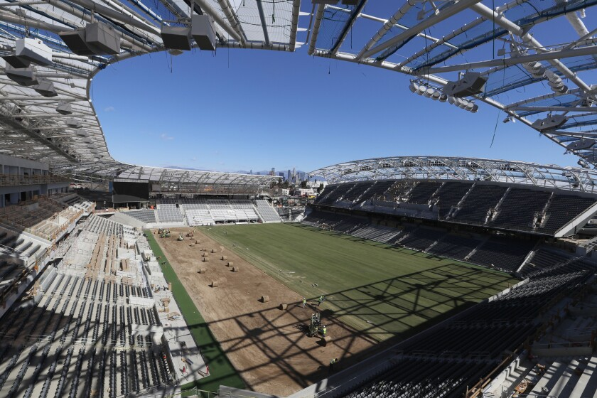 Workers install grass at LAFC's new Banc of California Stadium now under construction.