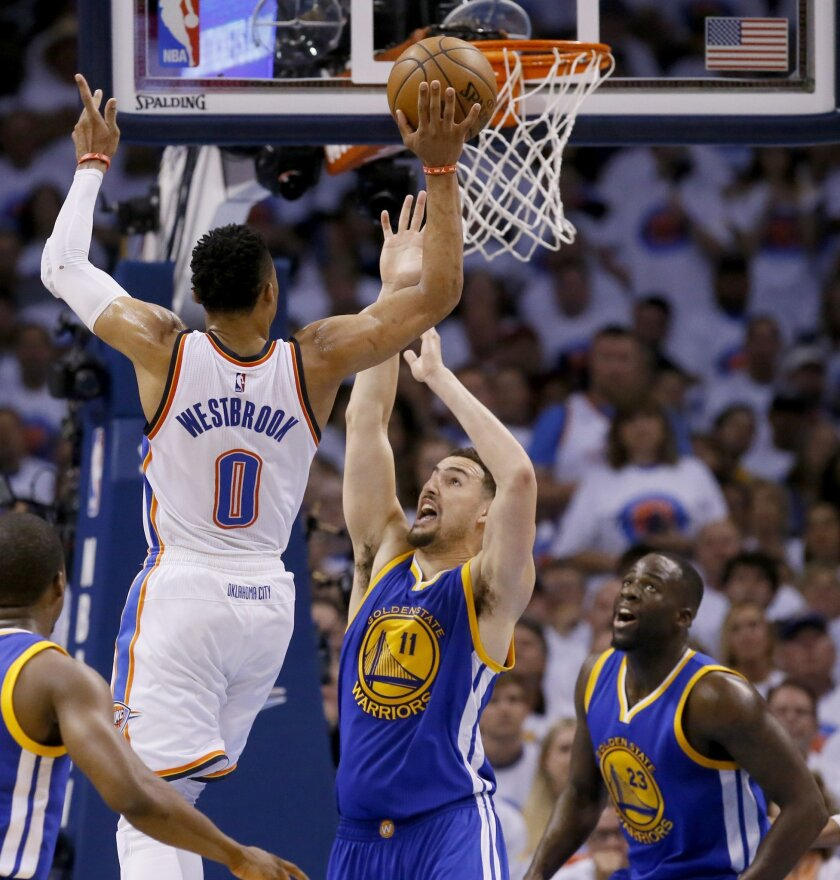Oklahoma City Thunder guard Russell Westbrook (0) shoots over Golden State Warriors guard Klay Thompson (11) during the first half in Game 4 of the NBA basketball Western Conference finals in Oklahoma City, Tuesday, May 24, 2016. Warriors forward Draymond Green (23) looks on. (AP Photo/Sue Ogrocki)