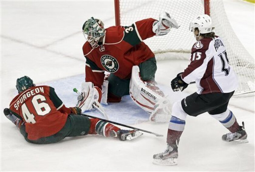 Minnesota Wild's Jared Spurgeon, left, comes to the aid of goalie Niklas Backstrom, of Finland, to stop a shot on goal as Colorado Avalanche's P.A. Parenteau, right, looks for a scoring opportunity in the first period of an NHL hockey game on Thursday, Feb. 14, 2013 in St. Paul, Minn. (AP Photo/Jim Mone)