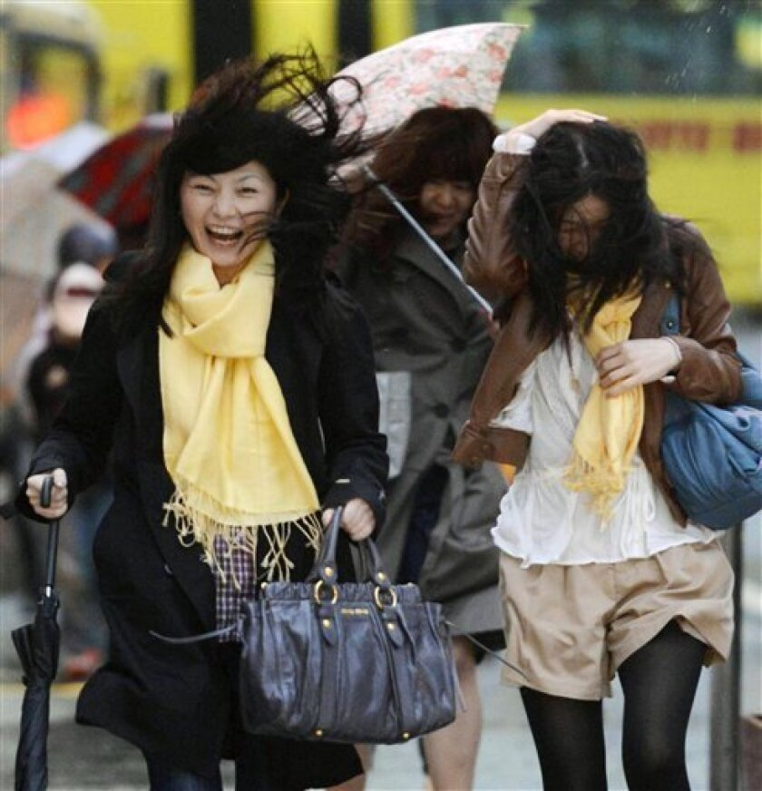 A woman reacts to a gust outside Tokyo train station in Tokyo Tuesday afternoon, April 3, 2012. A powerful rainstorm battered Japan Tuesday, paralyzing traffic and leaving thousands of homes without electricity. (AP Photo/Kyodo News) JAPAN OUT, MANDATORY CREDIT, NO LICENSING IN CHINA, HONG KONG, JAPAN, SOUTH KOREA AND FRANCE