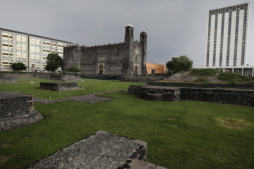 A Spanish colonial church, center, is surrounded by stone ruins and lawn, and is flanked by modern buildings