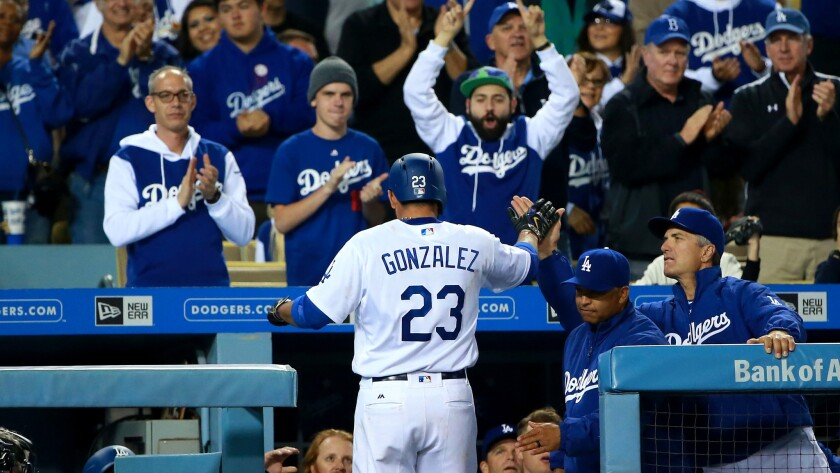 Adrian Gonzalez receives a standing ovation from Dodgers fans and high-fives from teammates and coaches after hitting a solo home run against the Diamondbacks in the fourth inning Wednesday.