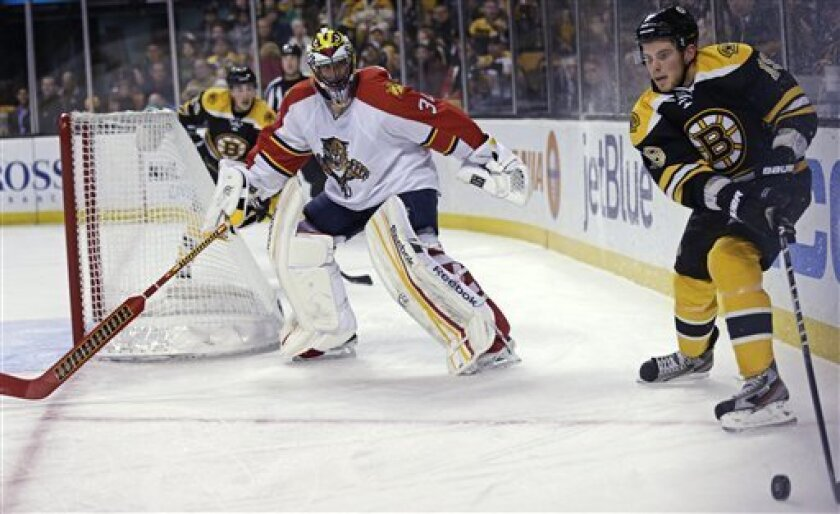 Boston Bruins center Tyler Seguin, right, looks to pass as Florida Panthers goalie Scott Clemmensen (30) skates away from the crease during the second period of an NHL hockey game in Boston, Thursday, March 14, 2013. (AP Photo/Charles Krupa)