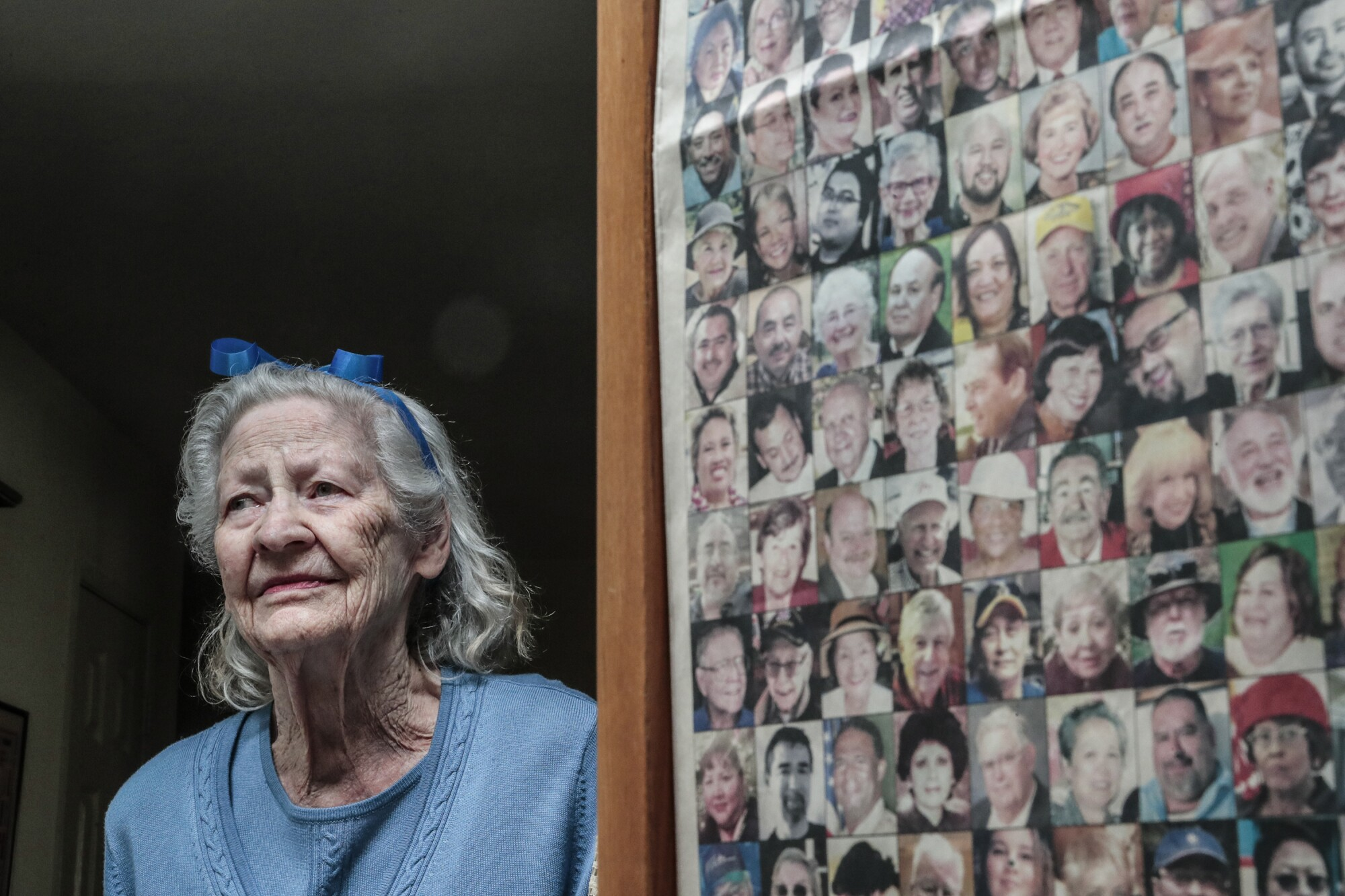 A woman stands next to a page of photos