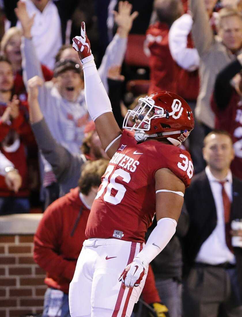 Oklahoma fullback Dimitri Flowers (36) celebrates after running in a touchdown pass against Iowa State during the first quarter of an NCAA college football game in Norman, Okla., on Saturday, Nov. 7, 2015. (AP Photo/Alonzo Adams)