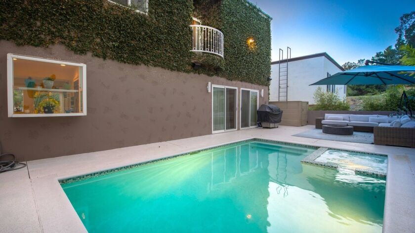 The Gates home has a patio with a swimming pool and hot tub