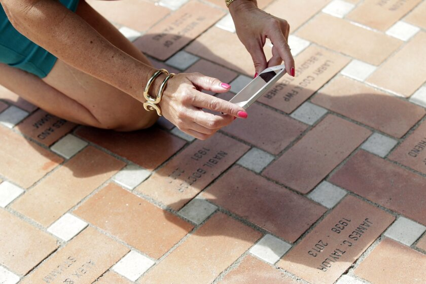 Debi Preece photograhs some of the bricks she purchased in honor of friends and family at the Main Library.