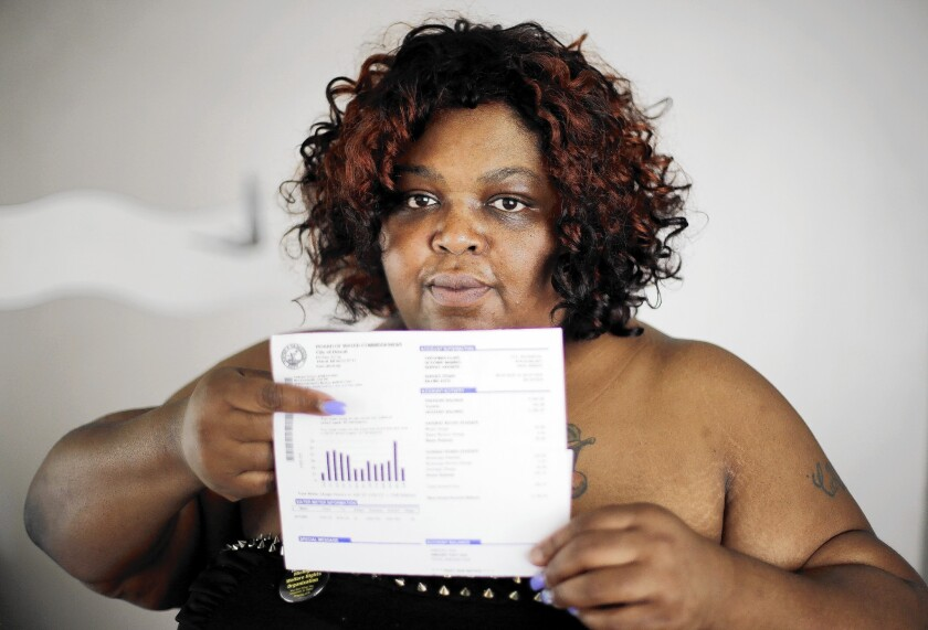 Nicole Hill holds up her past-due water bill at her home in Detroit. Her water has been off for about six weeks.
