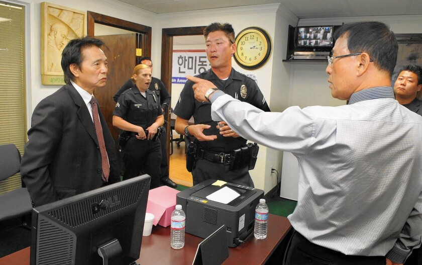 With police officers looking on, Sung Hoon Yoon, left, and Sung Woong Kim argue in the offices of the Korean American United Foundation in 2014. Yoon and Kim each claim to be the legitimate leader of the foundation.