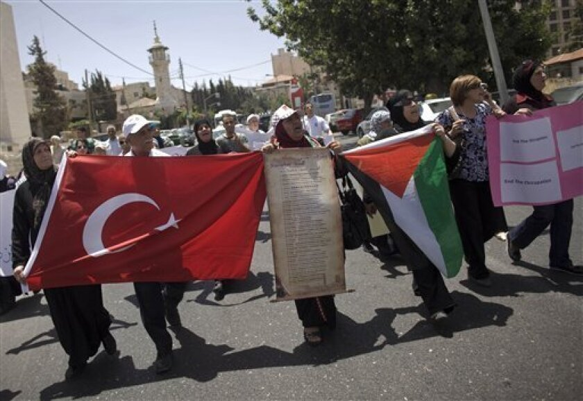 Palestinians signs as well as Turkish and Palestinian flags during a protest against the Israeli naval commando raid on a flotilla attempting to break the blockade on Gaza, in the east Jerusalem neighborhood of Sheikh Jarrah, Tuesday, June 1, 2010.  Some activists seized by Israeli authorities in t