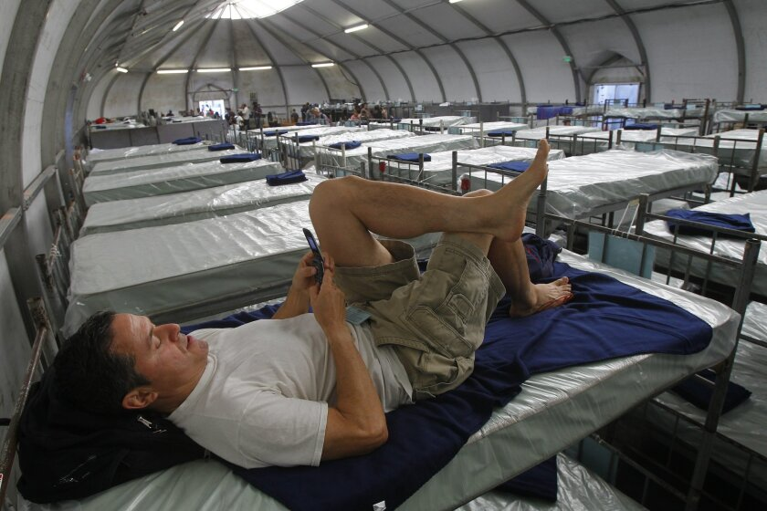 Robert Rivera relaxes on his bunk at the City of San Diego's emergency winter shelter for homeless adults on Friday in San Diego, California. Alpha Project operates the facility. Rivera says he became homeless when he lost his job after a work related injury.
