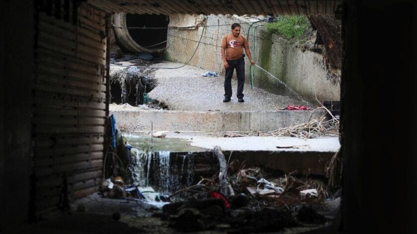 A man on the Mexican side of a culvert, where sewage flows in from Mexico, sprays a hose in Goat Can