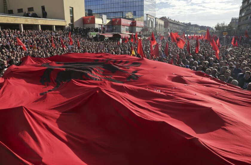 A massive Albanian flag is carried on top of tens of thousands of Kosovo opposition supporters during anti-government rally in Kosovo's capital Pristina on Wednesday, Feb. 17, 2016. Kosovo opposition supporters called for the government to resign Wednesday on the eighth anniversary of the country's