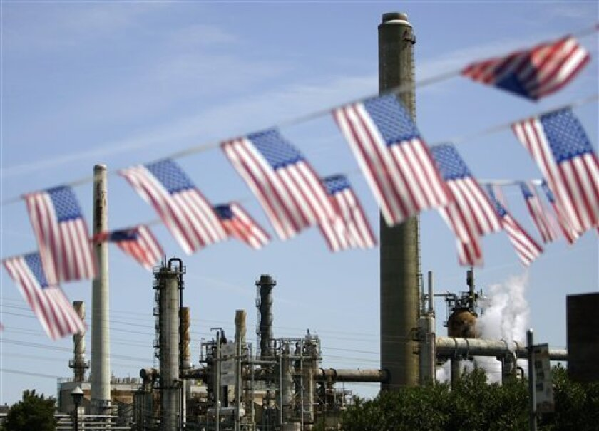 "FILE - In this April 30, 2008 file photo, American flags are seen near the Shell refinery, in Martinez, Calif. On Weds., Nov. 14, 2012, California's largest greenhouse gas emitters will for the first time begin buying permits in a landmark ""cap-and-trade"" system meant to control emissions of heat-t"