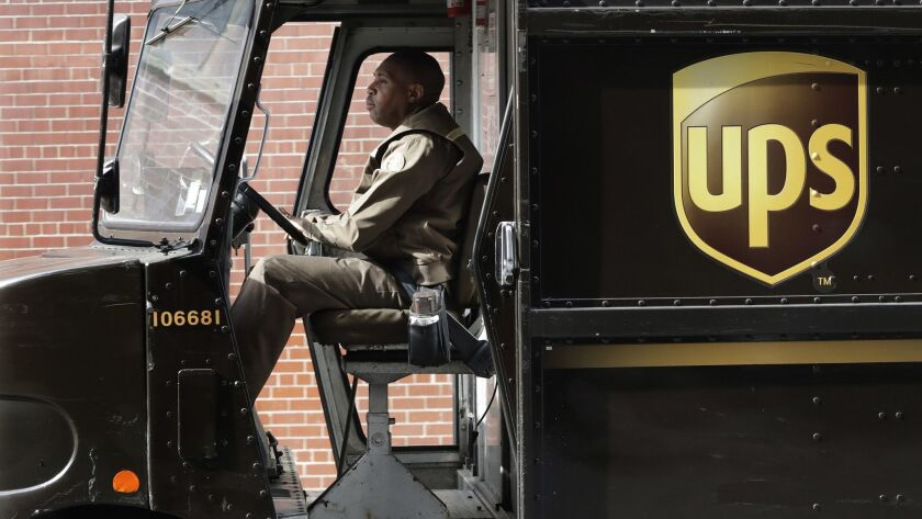 A UPS driver takes his truck on a delivery route in in 2017.