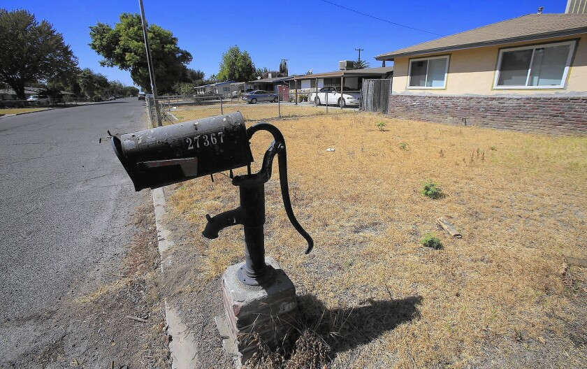 A mailbox mounted on a water pump sits amid a dead lawn in Parkwood in Madera County. The town's last well dried up in July.