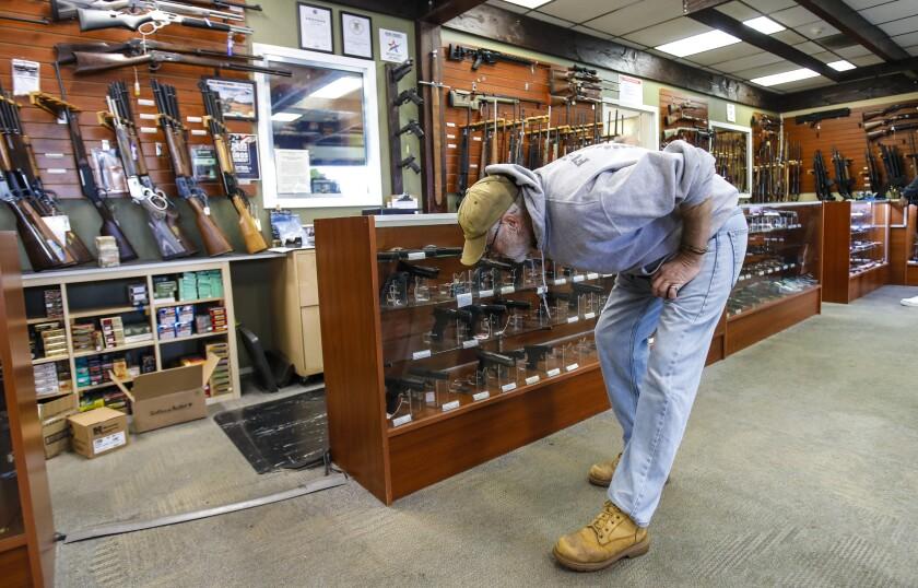 A customer shops for a gun at AO Sword Firearms in El Cajon in March.