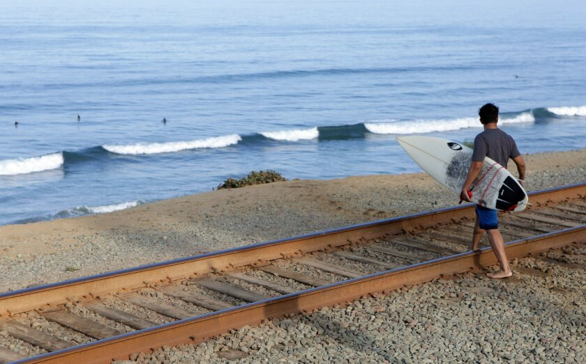 A surfer crosses the railroad tracks at 11th Street in Del Mar on Friday.