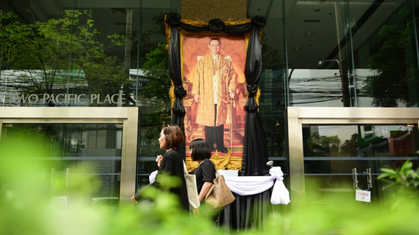 Thais clad in black walk past an image of the late King Bhumibol Adulyadej on one of the main streets in Bangkok on Sunday.