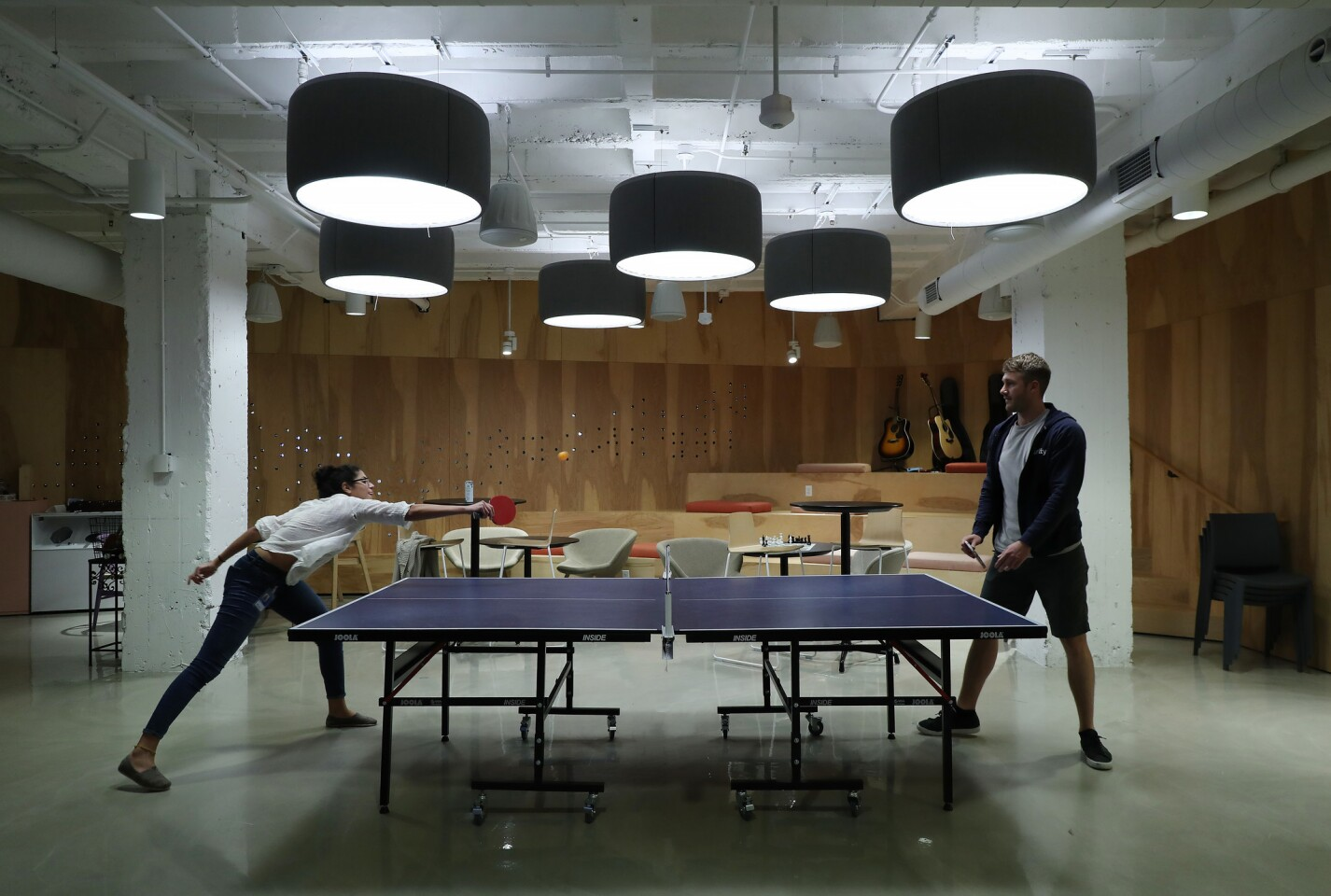 Arity employees Jade Isaac, left, and Max Plokita play table tennis at the company's office inside the Merchandise Mart Tuesday, June 19, 2018, in Chicago.