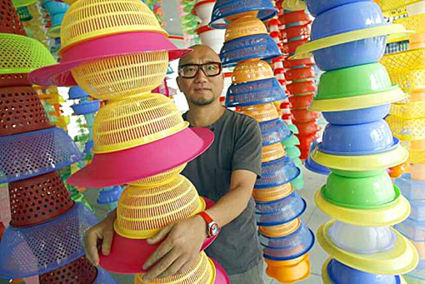 "IN THE THICK OF IT: Korean artist Choi Jeon-Hwa stands amid his installation ""HappyHappy,"" created from raw materials he purchased at a 99 Cents Only Store in L.A."
